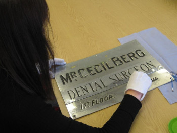 Curator working on object - a steel plate marked Mr Cecil Berg, Dental Surgeon