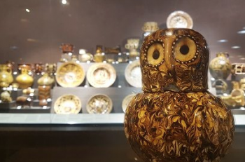 Pottery display with ceramic owl in foreground